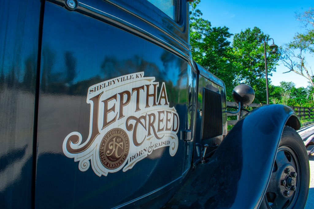 Jeptha Creed logo on classic car - reflection of distillery in side of vehicle